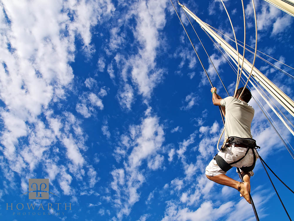 A sailor hoists himself up the rigging of spirit under the clear blue skies