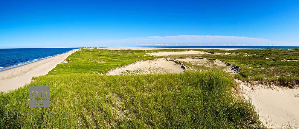 A panoramic image showing the vast, flat, grass and sand dunes of Sable Island