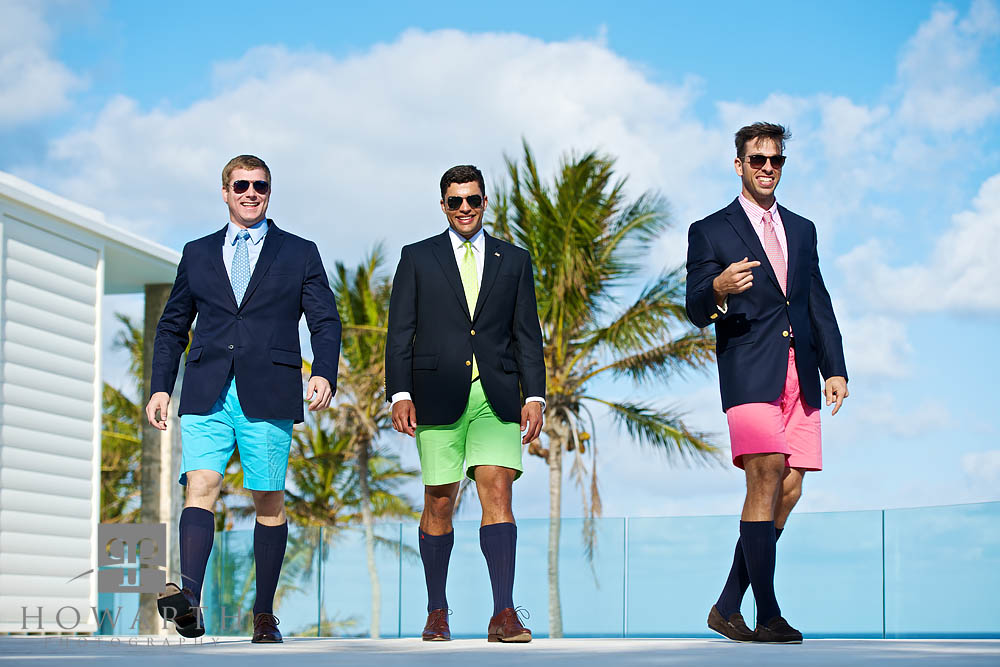 Three young professionals walking together; smiling and laughing while wearing brightly colored blue, green and pink Bermuda...