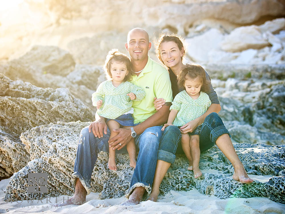 Mother and Father sitting on the limestone rocks on the beach with their young twin daughters