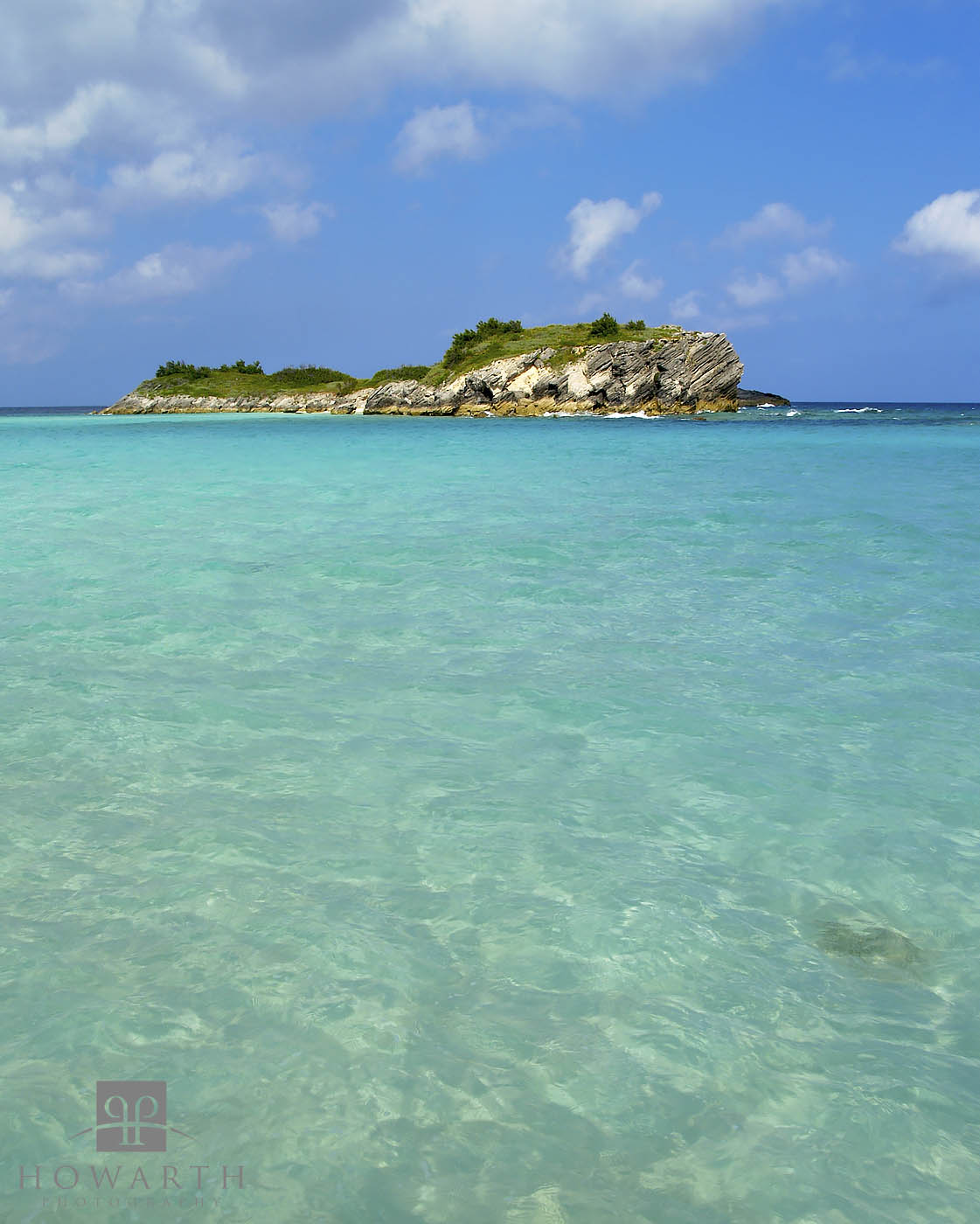 Turquoise waters lead to Charles Island under blue skies